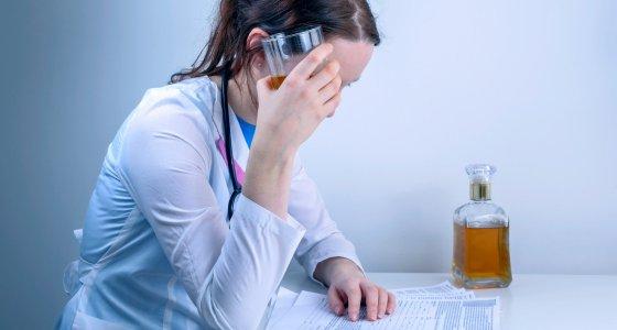 junge Ärztin trinkt Alkohol /penyushkin, stock.adobe.com