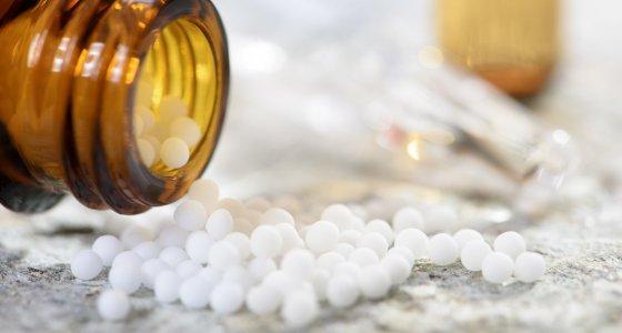 Braune Arzneimittelflasche mit weißen Globuli. /Wolfilser, stockadobecom