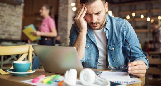 Student mit Kopfschmerzen beim lernen im Cafe /Jelena stock.adobe.com