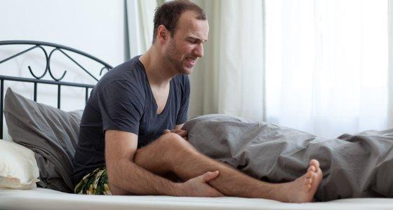 Mann sitzt im Bett und fasst sich vor Schmerzen ans Bein. /dpa