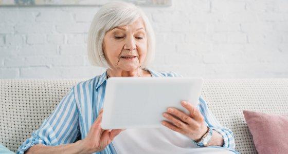Ältere Damem sitzt auf dem Sofa mit einem Tablet. /Lightfield Studios, adobe.stock.com