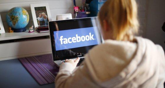 Mädchen sitzt vor einem Laptop, um facebook zu nutzen. /dpa