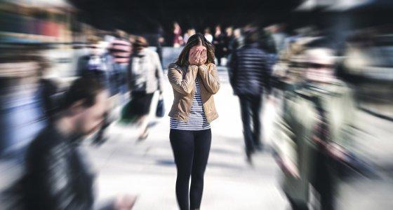 Frau steht in einer Menschenmenge und hält die Hände vor den Augen. /terovesalainen, stockadobecom