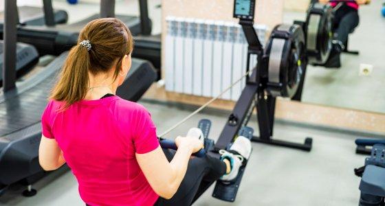 Junge Frau trainiert auf einer Rudergerät im Fitnessstudio /Yakov, adobe.stock.com