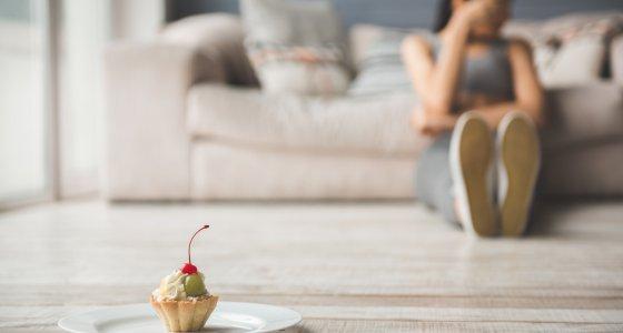 Junge Frau sitzt auf dem Boden, vor ihr ein Törtchen. Sie hält Diät. /VadimGuzhva stock.adobe.com