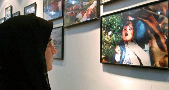 Eine Kurdin schaut sich am Rande einer Gedenkfeier für die Toten von 1988 im irakischen Halabdscha eine Fotoausstellung an, die das Grauen von damals dokumentiert. /picture alliance