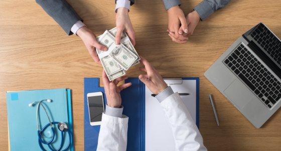 Einem Arzt wir Geld übergeben. /stokkete, AdobeStock.com