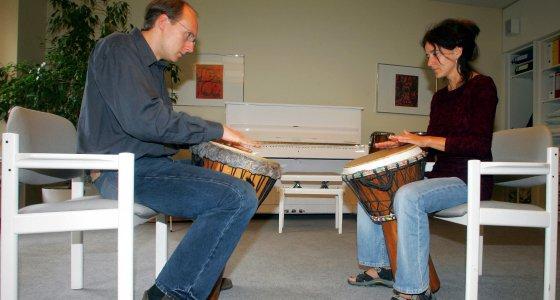 Auf einem Stuhl sitzend, trommelt der Musiktherapeut Jens-Peter Rose (l) in der Klinik für Tumorbiologie in Freiburg gemeinsam mit einer seiner Patientinnen (2005) /picture alliance