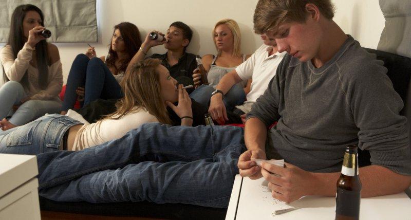 Jugendliche sitzen zusammen, trinken Alkohol, rauchen und drehen einen Joint. /Monkey Business, AdobeStock.com