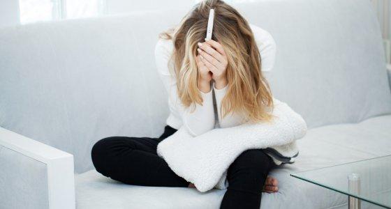 Verzweifelte Frau mit Schwangerschaftstest in der Hand /Maksymiv Iurii, AdobeStock.com