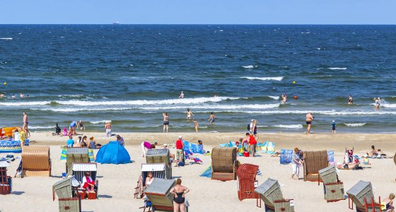 Strandkörbe und Badegäste am Meer. /katatonia AdobeStock.com