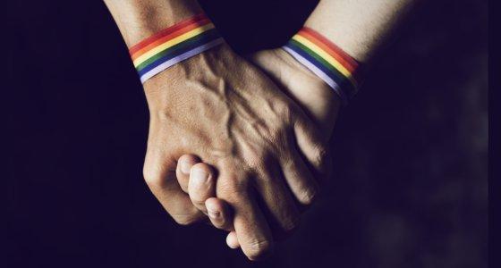 Männer halten sich an den Händen mit einem Armband mit Regenbogenmuster. /nito, Adobe.Stock.com