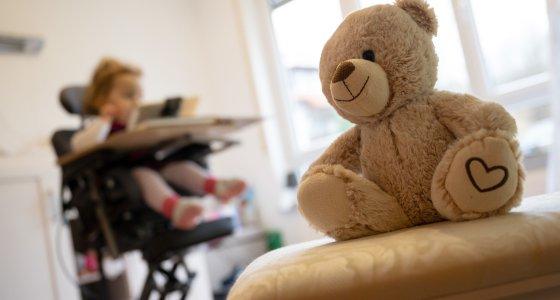 Backnang Ein Teddybaer sitzt vor einem Kind in einem Therapiestuhl das an spinaler Muskelatrophie SMA leidet