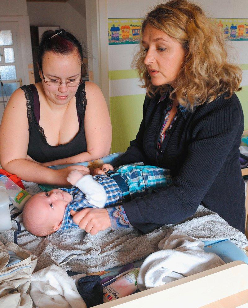 Eine Familienhebamme unterstützt im Rahmen der Frühen Hilfen eine junge Mutter mit ihrem Säugling. Foto: picture alliance/dpa/Holger Hollemann