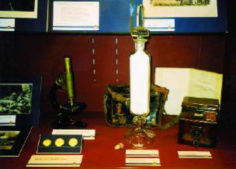 Robert Koch: zerriebene Tuberkel-Bazillen; links: Mikroskop zur Untersuchung von Bakterienkulturen, rechts: Plattenkamera aus Holz aus dem Besitz Robert Kochs. Oben rechts: Paul Ehrlichs Salvarsan
