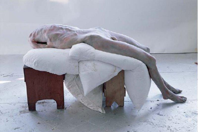 """Berlinde De Bruyckere: """"Pieta"""", 2007–2008, Wachs, Epoxidharz, Metall, Holz, Kissen, 126 × 60 × 188 cm: Auf zwei Holzschemeln ruht, von dicken Polstern gestützt, der totenblasse, nackte Leib eines Mannes. Obwohl dem Körper Kopf und Arme fehlen, fließt kein Blut, sind keine offenen Wunden erkennbar. Mit dieser versöhnlichen Symbolik versieht die belgische Künstlerin ihre der christlichen Tradition entlehnte Leidens- und Todesgestalt – Ausdruck eines universellen Gefühls von Schmerz. In der lebensgroßen Plastik, die an ein medizinisches Wachsmodell erinnert, verbinden sich Verstümmelung, Qual und Gebrochenheit zu einem erschütternden Menschenbild, das trotz aller Entblößung und Verletzung Würde ausstrahlt. © Friedrich Christian Flick Collection; Foto: Stiftung Moritzburg"""