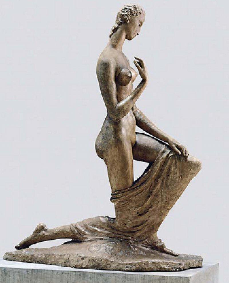 """Wilhelm Lehmbruck: """"Kniende"""", 1911, Gipsguss mit lackartigem Überzug, 179 × 71 × 141 cm: Auf Augenhöhe kniet sie vor dem Betrachter – die langgliedrige nackte Frau, die an eine mittelalterliche Mariengestalt erinnert. Trotz ihrer 100 Jahre ist sie auch heute noch äußerst attraktiv. Lehmbruck vermerkte auf der Rückseite ihrer Fotografie """"Kniende, überlebensgroß"""", denn stehend würde sie ihr Gegenüber weit überragen. Der Dialog, zu dem sie einlädt, entwickelt sich über die Körpersprache und nicht den Augenkontakt, denn sie hält den Blick gesenkt. Durch ihre aufrechte Haltung und das linke stehende Bein wirkt sie stolz, selbstbewusst. Der fein geformte Kopf und die anmutig vor der rechten Brust erhobene Hand unterstreichen den Zustand der inneren Ruhe. Gleichzeitig lässt uns der Bildhauer an ihrer Bewegung teilhaben. Er hat genau den Moment eingefangen, in dem sie wie eine Primadonna das Knie beugt oder sich aus dem Knicks erhebt. Foto: LehmbruckMuseum/Thomas Riehle"""