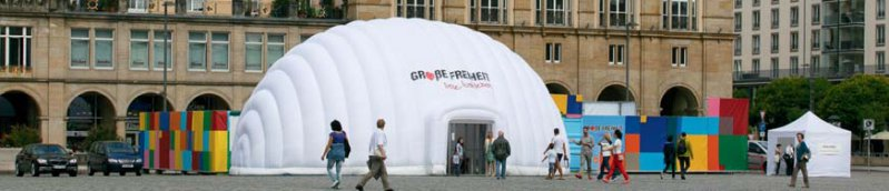 Ein weißes aufblasbares Zelt und sechs bunte Seecontainer laden Passanten und Besuchergruppen unentgeltlich zum Entdecken ein.
