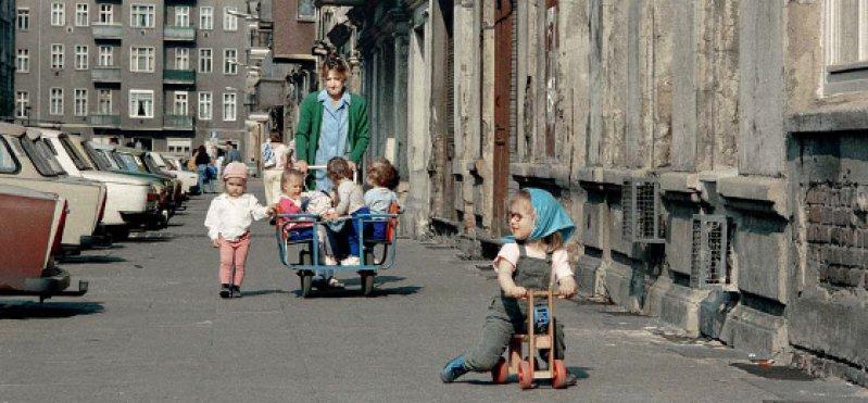 Eine Erzieherin macht einen Ausflug mit Kitakindern im sogenannten Krippenwagen im Ostberliner Bezirk Prenzlauer Berg um 1990. Foto: dpa
