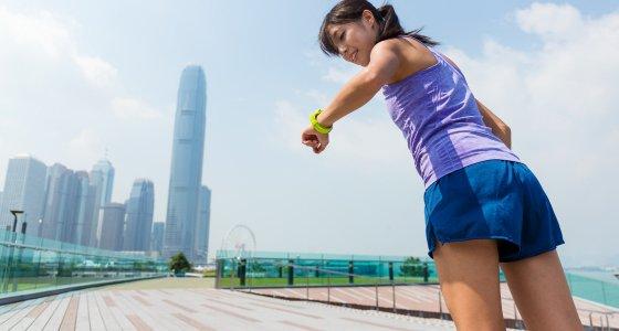 Joggende Frau auf einer Brücke betrachtet ihr Fitnessarmband/ leungchopan, stock.adobe.com