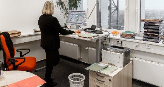Technische Hilfen wie ein höhenverstellbarer Schreibtisch können von der Bundesagentur für Arbeit bezuschusst werden.